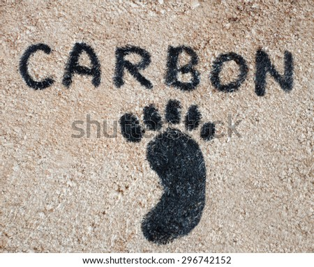 Global warming concept with black carbon footprint on wood background - stock photo