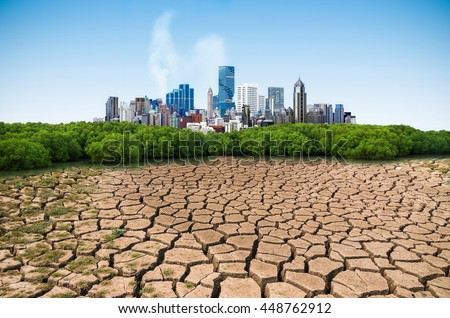 Global warming, Dry cracked earth with Pollution modern city. - stock photo