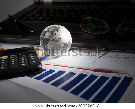 Globe and some business accessories on business documents with deep shadows. - stock photo
