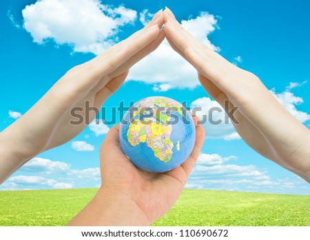 Globe earth in man's hand with female hands protecting it. World care concept