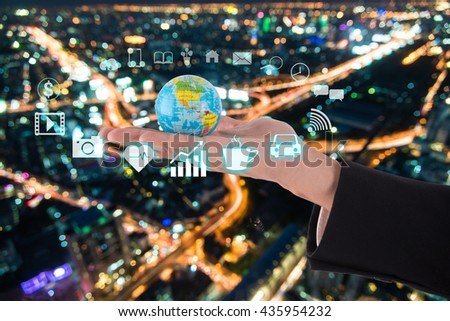 globe in businessman hand over night city background , internet of things concept