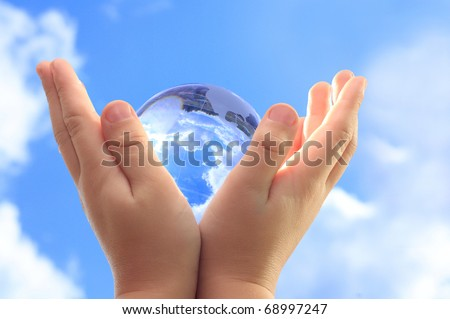 Globe in child hands against blue sky. - stock photo