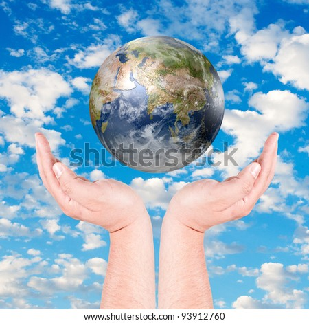 Globe in human hand against blue sky. Environmental protection concept. Data Source: NASA