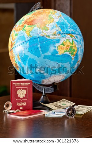 Globe, money, passport and compass are on the table - stock photo