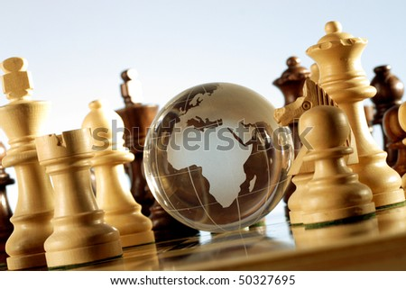 Globe on chess board - stock photo