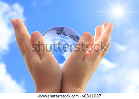 Globe on child hand against blue sky. - stock photo