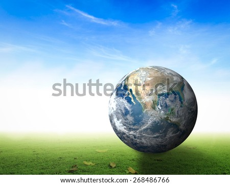 Globe on green grass over blurred blue sky background. Elements of this image furnished by NASA. - stock photo
