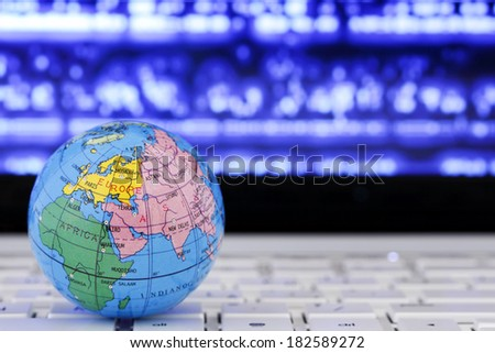 globe on laptop against abstract background - stock photo