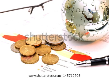 Globe puzzle and Euro coins on business document