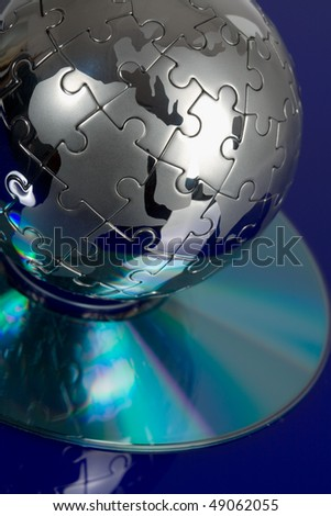 Globe puzzle with CD on blue background