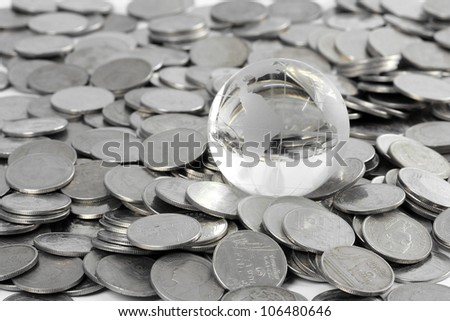 Globe staying on coins. money concept - stock photo