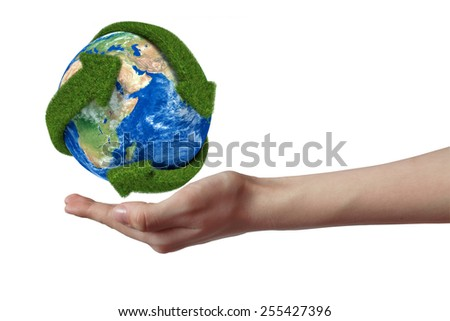 Globe with green arrows covered with grass presented - stock photo