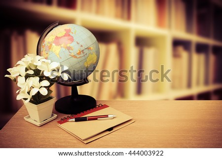 globe world and notepad with blur perspective bookshelf background - stock photo