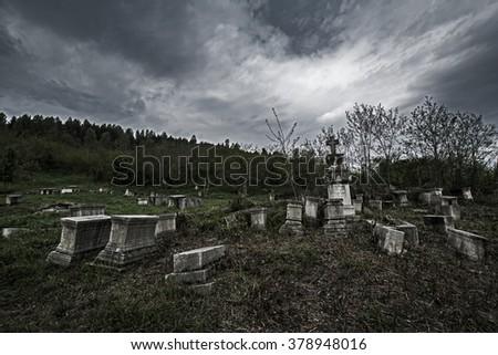 gloomy ancient cemetery under a dark sky - stock photo