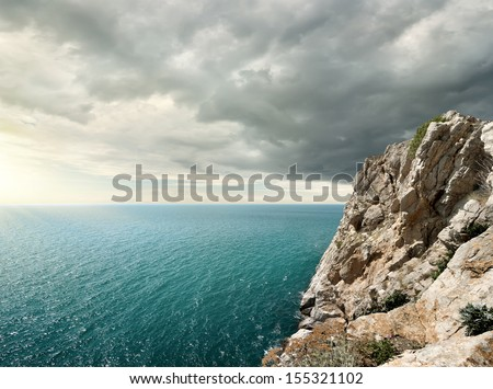 Gloomy clouds over the sea and rocky mountain - stock photo
