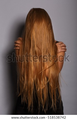Gloomy depressed woman in black clothes with long blonde hair covering her face embrace herself with her hands standing on grey background