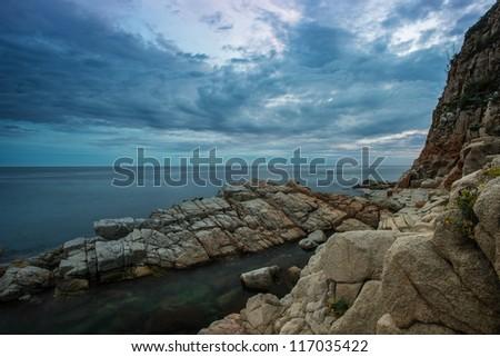 Gloomy sky over rocky shore - stock photo
