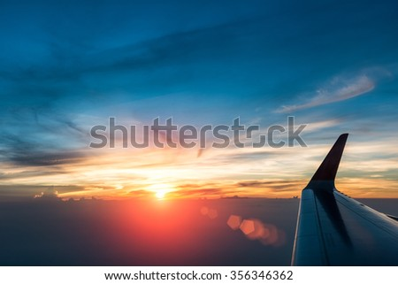 glorious sunset with plane wing in the air - stock photo
