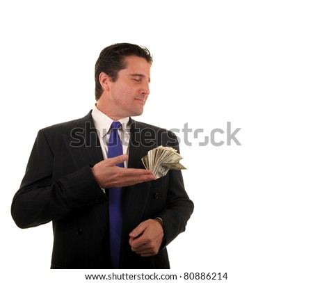 Glorying in job profit, a happy and greedy businessman smells the money the he made with his latest business venture. - stock photo