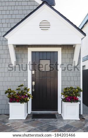 Glossy front door to a family home; The door is made of vertical wood boards, with a window. It is framed by two flower planters, gray shingles of the house, and a door mat.