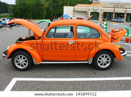 GLOUCESTER, VA- JULY 13: An orange VW Beetle in the (middle peninsula car club) blast from the past car show at the Main St shopping center in Gloucester, Virginia on July 13, 2013   - stock photo