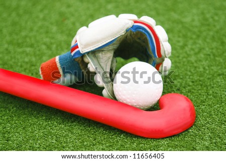 Glove with a red stick on green grass - stock photo