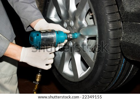 Gloved car mechanic hands removing wheel nuts to check brakes. - stock photo