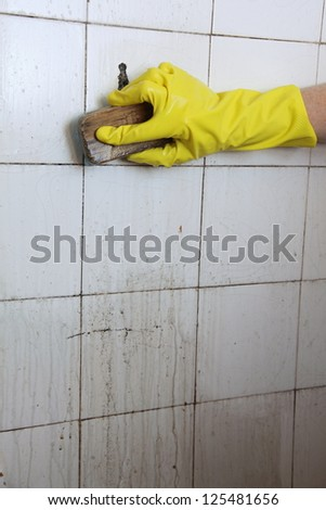 gloved hand cleaning dirty old tiles with brush in a bathroom - stock photo