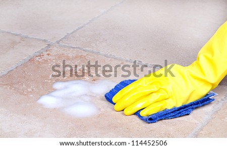 gloved hand cleaning tile with cloth or rag - stock photo