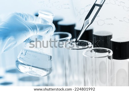 gloved hand hold a flask in laboratory room - stock photo