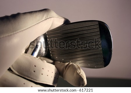 Gloved hand holding a golf iron