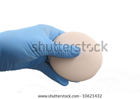 Gloved hand holding birth control pills in a pink circular dispenser - stock photo