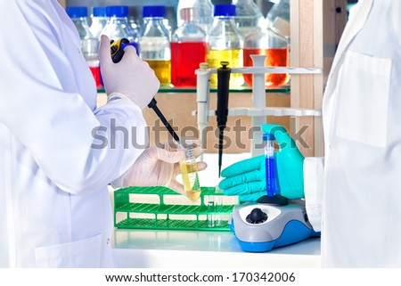 Gloved hand of a laboratory technician mixing chemical solutions in a test tube on a centrifuge with another colleague standing ready with an automated pipette. - stock photo