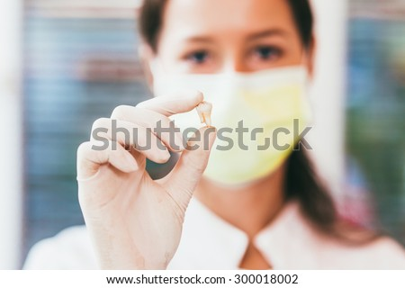 Gloved hand of dentist holding extracted tooth, close-up - stock photo