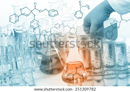 Gloved hand pour the solution from flask to another flask in laboratory with chemical equations background. - stock photo