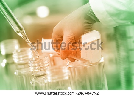 Gloved hand pour the solution from flask to test tube in laboratory. - stock photo