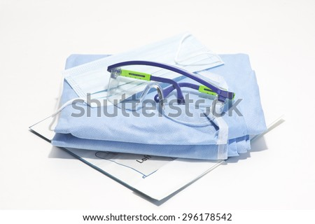 Gloves, mask, gown and safety glasses for personal protection during surgical procedures. - stock photo