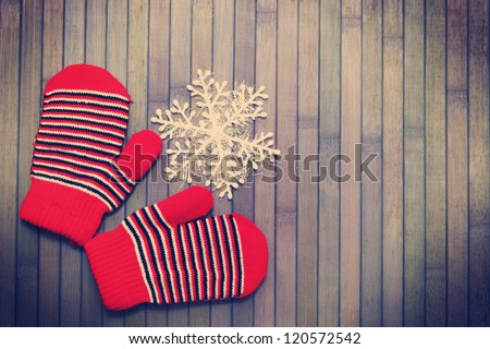 gloves with snowflake on a wooden background - stock photo