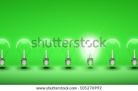 glow among other light bulb on a green background - stock photo