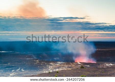 Glow of an erupting volcano at early sunrise at Hawaii Volcanoes National Park, Big Island, Hawaii - stock photo
