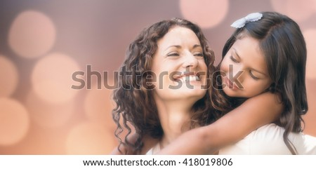 Glowing background against happy mother and daughter embracing - stock photo