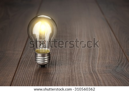 glowing bulb standing on the brown wooden background - stock photo