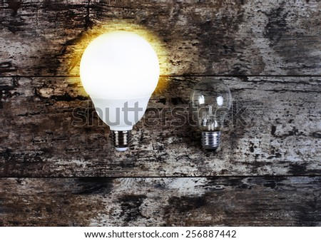 glowing bulb uniqueness concept on brown wooden background - stock photo
