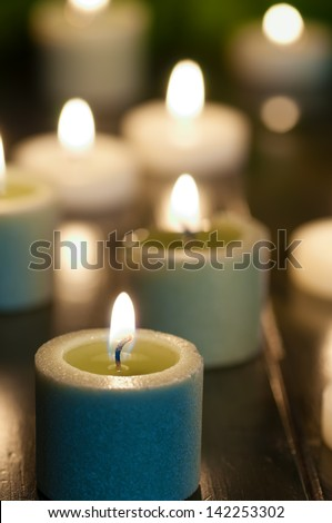 Glowing, Burning Candles in Spa, Religious, Romantic or Holiday Setting with Blurred Background, Vertical Closeup - stock photo