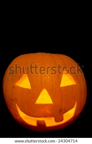 Glowing Candle Lit Halloween Pumpkin Head Carved Jack O Lantern, Cut Out on Black - stock photo