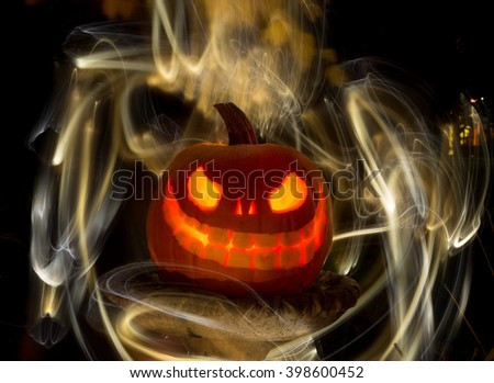 Glowing carved pumpkin or jack-o-lantern for Halloween in rustic setting with streaking lights - stock photo