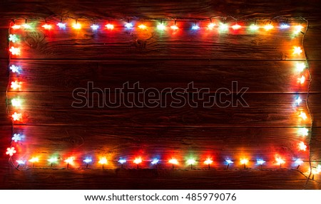 Glowing Christmas Lights Frame for Xmas Holiday Greeting Cards Design. Wooden Hand Drawn Background. Merry Christmas.