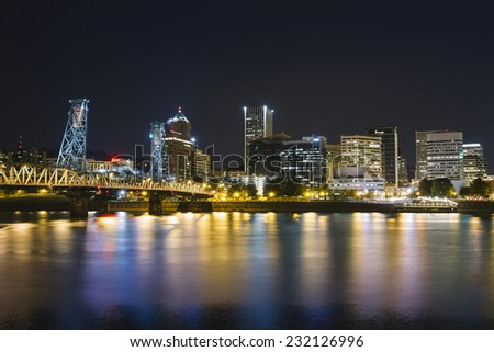 Glowing city lights in Downtown Portland with Hawthorne bridge and water reflections - stock photo