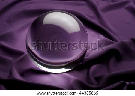 glowing crystal ball shot on purple satin - stock photo