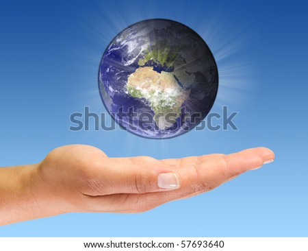 Glowing Earth on open palm - stock photo